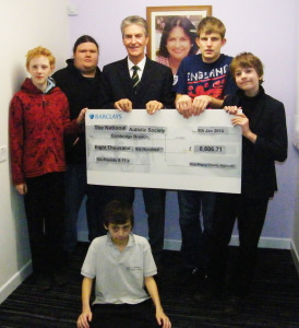Mr Ivan Robinson (centre), the 2013 Captain of the Gog Magog Golf Club, presenting a cheque for £8,606.71 to representatives of autistic community.